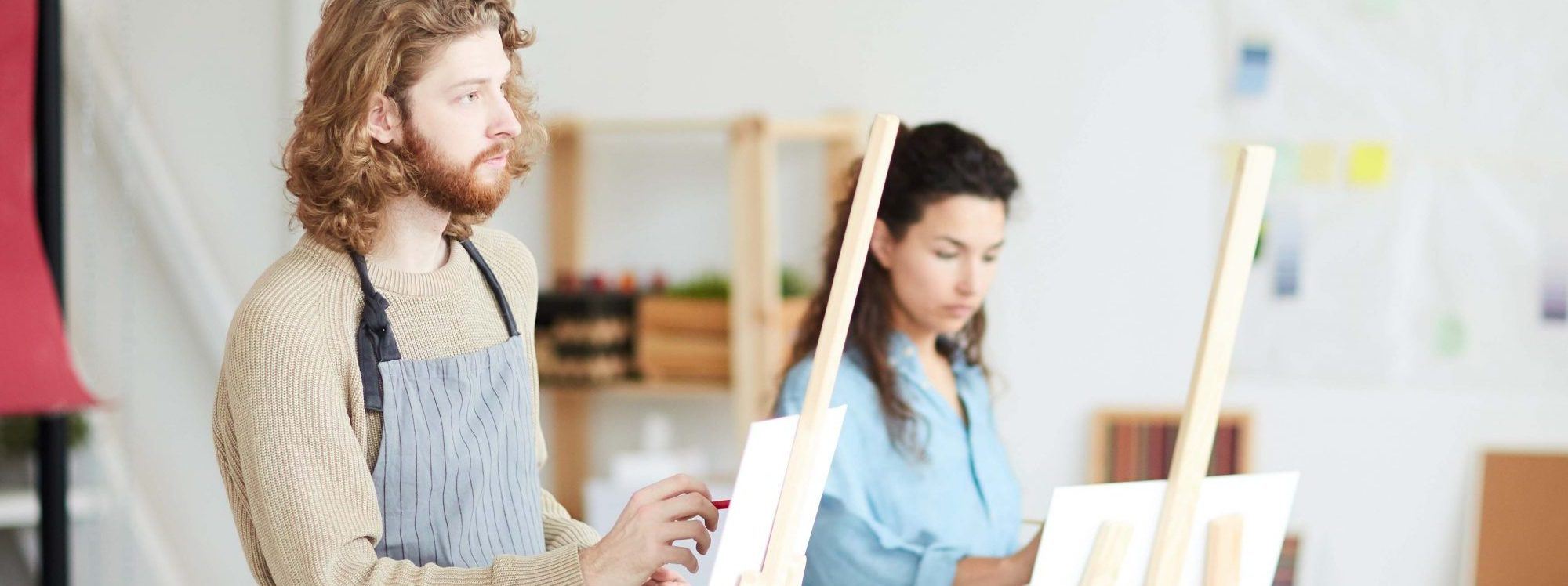 Young pensive artist getting inspired while standing in front of easel and painting in studio